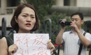 Esposa de activista chino protesta trato que dan a su marido